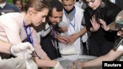 Президент Башар Асад с супругой укладывают гуманитарную помощь для пострадавших в Хомсе