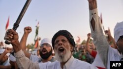 Pakistani supporters of Canada-based preacher Tahir-ul Qadri shout anti-government slogans during a protest in front of the Parliament in Islamabad on August 27, 2014.