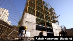 Labourers work at the construction site of a building in Tehran