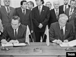 Председатель Верховного совета СССР Борис Ельцин (справа) и президент Казахстана Нурсултан Назарбаев подписывают договор в Москве. 21 ноября 1990 года.