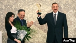 "Azerbaijani President Ilham Aliyev holds his ""Friend of Journalists"" Award aloft at a ceremony in Baku on December 29."