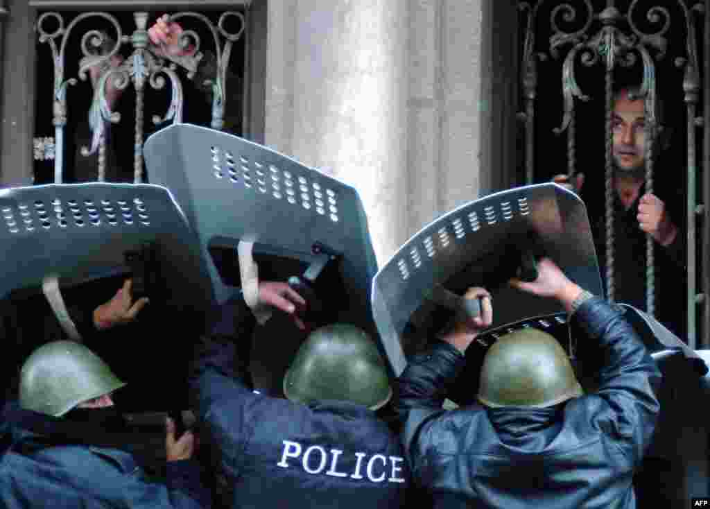 Georgian police guard the entrance of the parliament building in Tbilisi while opposition supporters storm it on November 22.