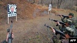 Солтүстік Корея әскерлері Оңтүстік Корея қорғаныс министрі Ким Кван Джин мен АҚШ сарбазының суретін атып жаттығып жатыр. Сәуір, 2013 жыл.