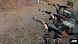 گروهی از سربازان کره شمالی در حال تیراندازی به پوستر رهبران کره جنوبی و آمریکا