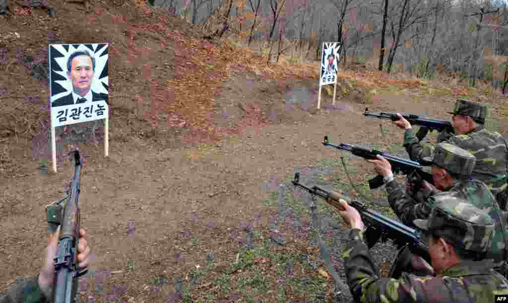 This photo provided by North Korea's official Korean Central News Agency shows North Korean soldiers shooting at targets carrying the images of South Korean Defense Minister Kim Kwan-Jin (left) and a U.S. soldier at an undisclosed location. (AFP)