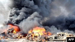 Smoke rises from burning cars at the site of twin blasts in Damascus on May 10.