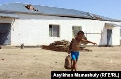 Местный мальчик несет воду в пятилитровой бутылке. Село имени Комекбаева Кызылординской области.
