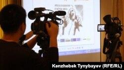 Телевизионный оператор настраивает видеокамеру на проекционный экран. Иллюстративное фото.