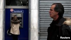 Yunan qadın bankomatdan pul çıxarır.