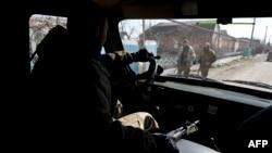 Сепаратист с оружием в машине проезжает мимо других проходящих вооруженных боевиков. Село Широкино, десять километров от Мариуполя. 20 марта 2015 года.