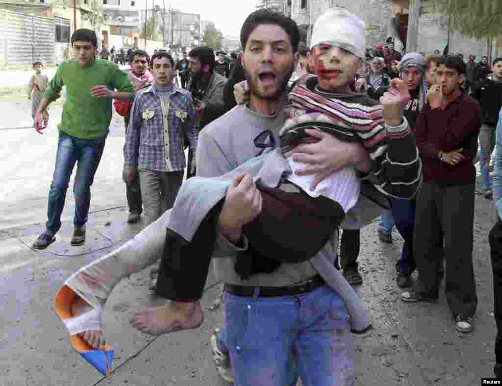A man carries a child who was wounded after a missile hit the al-Myassar neighborhood of Aleppo, Syria. (Reuters/Muzaffar Salman)
