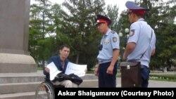 Полицейские разговаривают с Эриком Жумабаевым во время проведения им акции протеста с требованием освободить политзаключенных. Уральск, 12 августа 2019 года.
