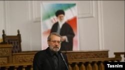Iran Parliament Speaker Ali Larijani speaking under a poster of Ayatollah Ali Khamenei