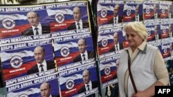 """A woman walks past posters showing Russian President Vladimir Putin reading """"Welcome, President"""" in Belgrade on October 15."""