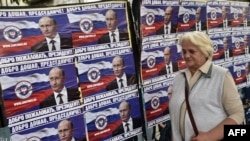 "A woman walks past posters showing Russian President Vladimir Putin reading ""Welcome, President"" in Belgrade on October 15."