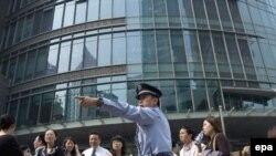 یک مامور پلیس مردم وحشتزده را که از ترس زلزله به خیابان ریخته اند، هدایت می کند. (عکس: EPA)