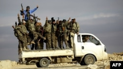 Fighters from the Arab-Kurdish alliance, known as the Syrian Democratic Forces, wave from a truck driving through on the western outskirts of the Islamic State bastion of Raqqa in Syria. (file photo)