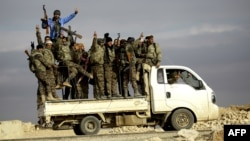 Fighters from the Kurdish-Arab alliance, known as the Syrian Democratic Forces, wave from a truck driving through the village of Al-Haymar, located on the western outskirts of the Islamic State (IS) bastion of Raqqa, in December.