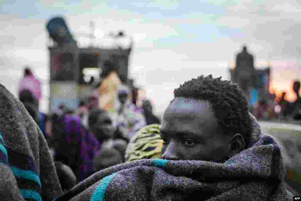 A displaced man tries to keep warm as the belongings of people fleeing violence in the Bor region of South Sudan are unloaded at Minkammen. (AFP/Nichole Sobecki)