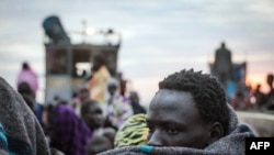 A displaced man tries to keep warm as the belongings of people fleeing violence in the Bor region of South Sudan are unloaded at Minkammen.(AFP/Nichole Sobecki)