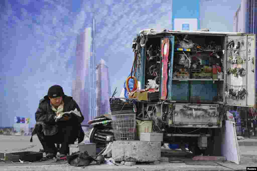 A man reads next to his makeshift bicycle repair cart along a road in Beijing's central business district. (Reuters/Jason Lee)