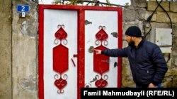 Arxiv fotosu: Nardaran sakini darvazada güllə izini göstərir