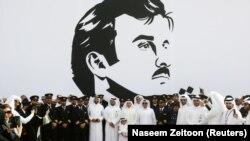 Политики, военные и бизнесмены Катара на фоне портрета своего правителя, эмира Тамима бин Хамада Аль Тани
