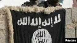 جنود عراقيون ينظرون الى علم تنظيم القاعدة خلال عملية تفتيش في منزل غرب بغداد 27/10/2011