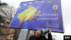 Priština, prolaznik pored bilborda na kojem piše Srećna peta godišnjica nezavisnosti, februar 2013.