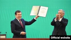 Shavkat Mirziyaev (left) is sworn as Uzbek president at a joint session of the parliament's two chambers in Tashkent on December 14.