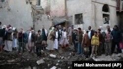 مردم در اطراف یک ساختمان دولتی یمن در صنعا پس از حمله هوایی به آن؛ ۱۱ نوامبر