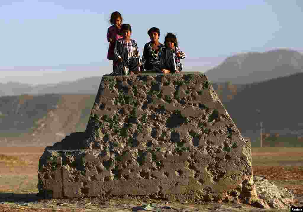 Afghan children sit on a bullet-riddled concrete block in Kabul on October 21. (Reuters/Mohammad Ismail)