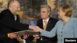 Мұхаммед пайғамбарға карикатура салған даниялық суретші Курт Вестергаардты (сол жақта) Германия канцлері Ангела Меркель (оң жақта) жүлдесімен құттықтап жатыр. Германия, Потсдам, 8 қыркүйек 2010 жыл.