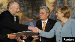 Danish cartoonist Kurt Westergaard (left) is congratulated on his prize by German Chancellor Angela Merkel (right) at the M100 Media Prize ceremony in Potsdam on September 8