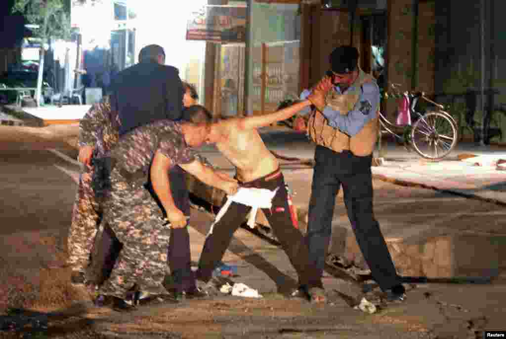 "Iraqi security forces are seen removing an explosives vest from a would-be suicide bomber -- a young boy -- in Kirkuk. The boy was apprehended late on August 21 shortly after a suicide bomb attack on a Shi'ite mosque in the city. ""The boy claimed during interrogation that he had been kidnapped by masked men who put the explosives on him and sent him to the area,"" Kirkuk intelligence official Chato Fadhil Humadi told AP. (Reuters/Ako Rasheed)"