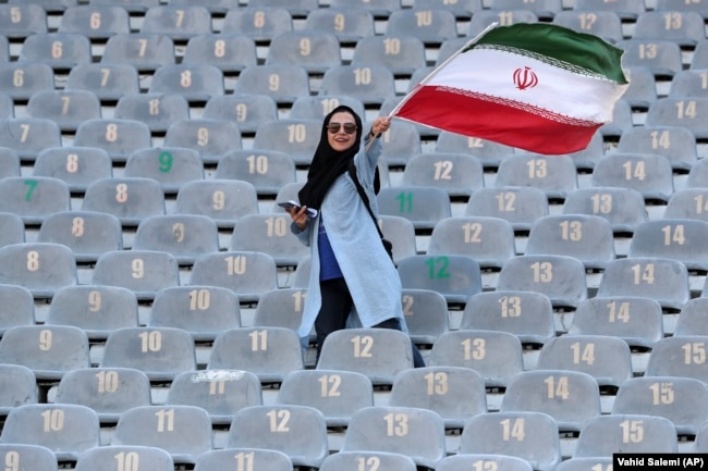 An Iranian woman waves her country's flag as she arrives at the Azadi Stadium to watch the 2022 World Cup qualifier soccer match between Iran and Cambodia, in Tehran, Iran, Thursday, Oct. 10, 2019.