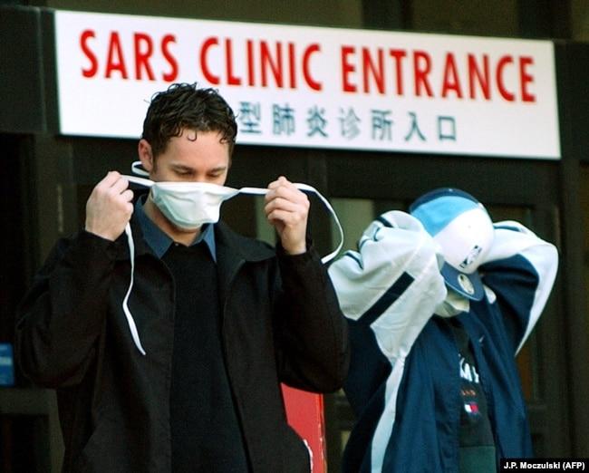 Канадада SARS диагнозы қойылған науқастар жатқан ауруханадан шығып келе жатқан адам. Торонто, 2003 жылдың наурызы.адец у клиники для пациентов с ОРВИ в Торонто, март 2003 года.