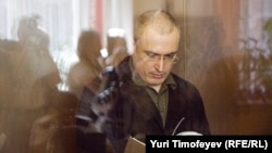 Russia -- Mikhail Khodorkovsky reads documents behind a glass wall during a court session in Moscow, 21Jun2010