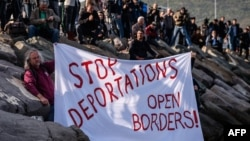 German activists show a banner during the arrival of a small Turkish ferry carrying migrants in Dikili on April 4.