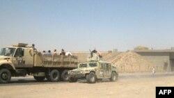 Иракские военнослужащие в гражданской одежде покидают город Киркук, 11 июня 2014 года