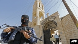 An AFP photo of Iraqi security staff guarding a church in Bartala, which IS supporters have used to claim the militant group is protecting Christian churches in the city of Mosul.