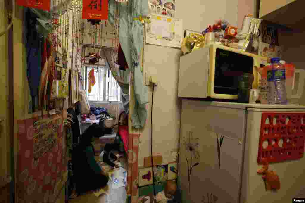 Michelle Wong, a single mother, plays with her 2-year-old daughter in the bedroom of their 8-square-meter subdivided flat in a district of Hong Kong. (2012 photo)