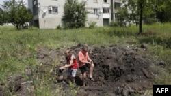 Діти у прифронтовому місті Попасна, контрольованому урядом, грають у вирві, залишеній снарядом, Луганська область, 22 червня 2015 року
