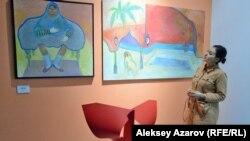 Муниса Гулиева рядом с двумя своими картинами. Картина слева называется «Принцесса Анис», и на ее создание вдохновила черно-белая фотография иранской принцессы в балетной пачке и с мужским лицом. Вокруг этой фотографии возник спор — сама ли это принцесса, или же один из охранников гарема.