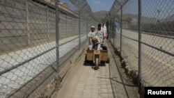 Men coming from Afghanistan move down a corridor between security fences at the border post in Torkham on June 19.