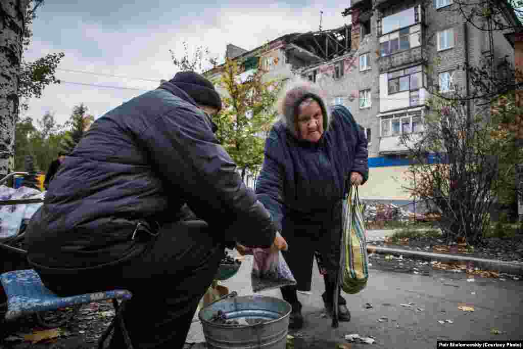 Nikolai sells grapes, grown in his own garden, to an elderly woman in front of a destroyed building in Gorlovka. According to the new separatist mayor, 80 percent of the city's population has returned to their homes. Job opportunities are still very limited