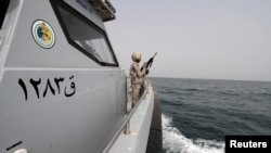SAUDI ARABIA - A Saudi border guard watches as he stands in a boat off the coast of the Red Sea on Saudi Arabia's maritime border with Yemen, near Jizan April 8, 2015