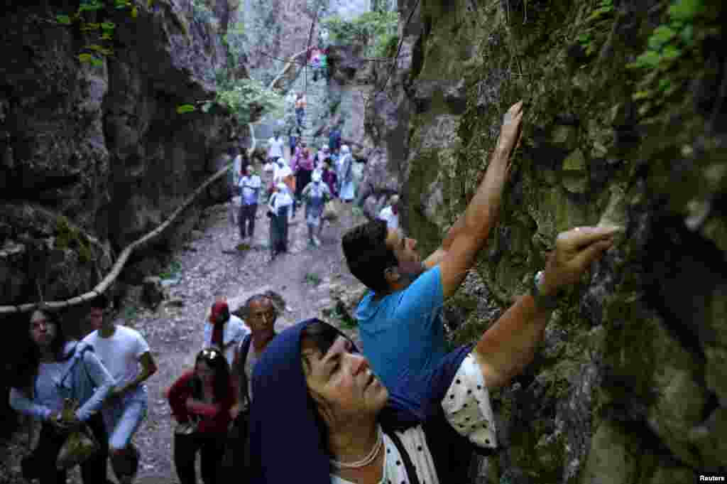 A Bosnian Muslim woman breaks off a piece of rock for good luck before commemorating the anniversary of Ajvatovica near the village of Prusac in Bosnia-Herzegovina. Ajvatovica is the largest traditional religious and cultural event of Bosniaks. (Reuters/Dado Ruvic)