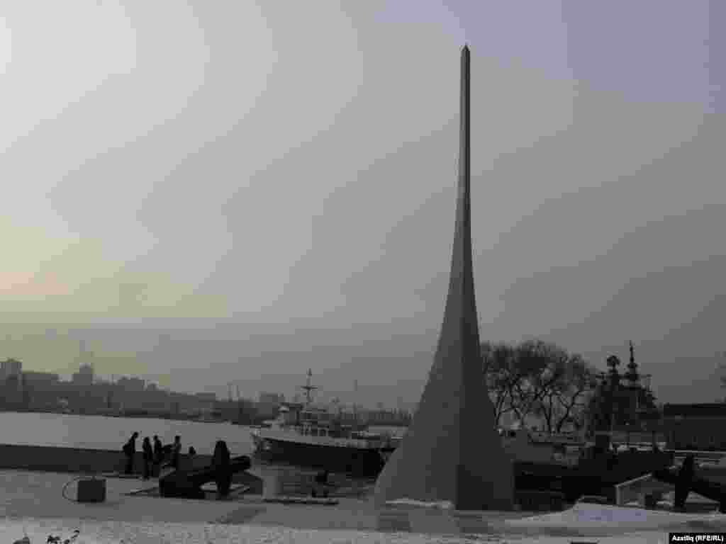 Диңгез ярында Владивосток төзүчеләренә һәйкәл. Һәйкәл көймә алды рәвешендә эшләнгән, янында якорьләр ята. 1860-1895 еллар.
