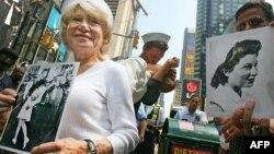 Женщина на Таймс-сквер держит фотографию «Поцелуй». Нью-Йорк, 11 августа 2005 года.